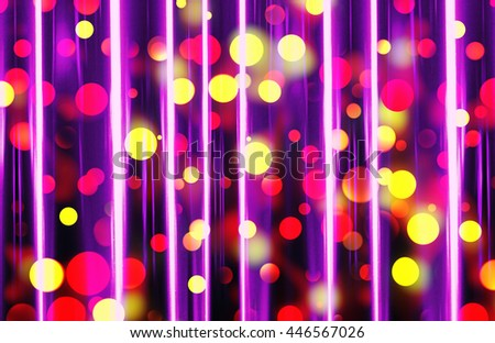 A brightly illuminated festive bokeh design in shades of red and yellow seen through a sheer purple curtain - stock photo