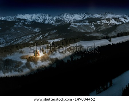 A brightly lit Christmas tree glows with warm light and the Christmas spirit on a cold winter night in the Colorado Rocky Mountains. - stock photo