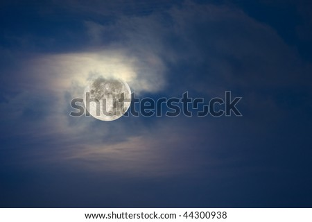 A brightly lit full moon lights up the cloudy, hazy sky.