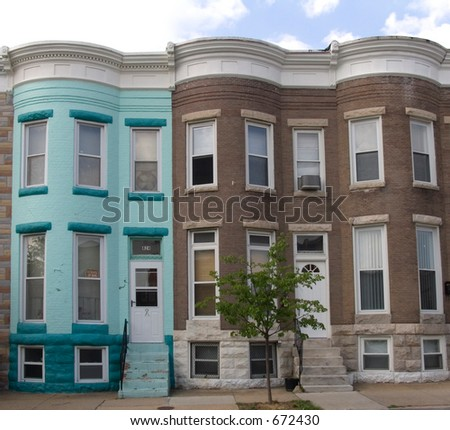 A brightly painted blue rowhouse stands out on a street of plain brick rowhouses.