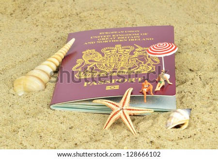 A British passport on the beach with mini holiday makers