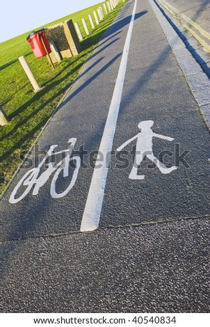 A British pavement, divided and signed for cyclists and pedestrians between an open field and a road.  Sunny day, blue sky. - stock photo