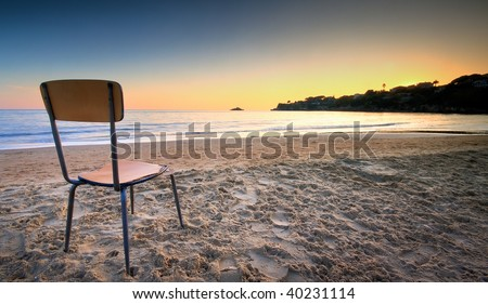A broken and old chair left on the sand at the beach pointed to the sunset behind a hill. The concept of loneliness and missing - stock photo