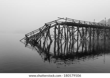 A broken down wooden bridge  in the river - stock photo