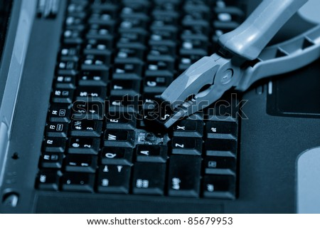 A broken laptop with a pliers. Closeup