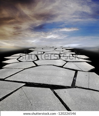 A broken pavement leading into a surreal apocalyptic sky for the concept of a dangerous hard journey forward. - stock photo