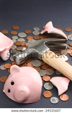 A broken piggy bank loaded with coins. Copy space available. Business & finance concept. - stock photo