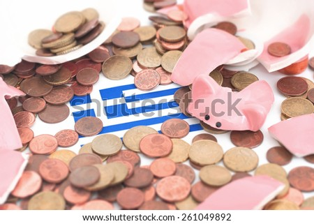 A broken Piggybank with the Flag og greece in the middle of the picture . 