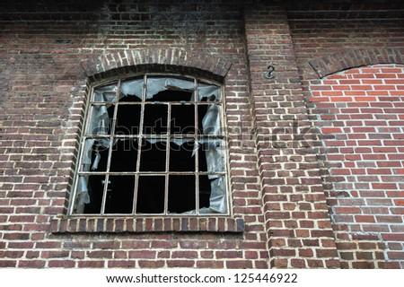 A broken window in old worn down building - stock photo