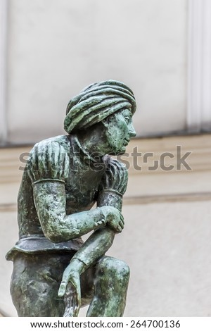 A bronze statue of a poor student near St Mary's Basilica - a replica of Wit Stwosz (German sculptor, Veit Stoss) sculptures in famous gothic altar of Basilica (Kosciol Mariacki). Kracow, Poland. - stock photo