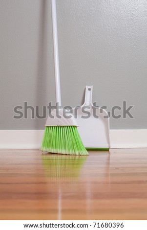 A broom and dust pan on New Hardwood Flooring - stock photo
