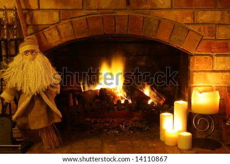 A broomstick Santa Claus by a log fire, with candles.