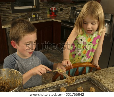 A brother and a sister making oat meal cookies in their kitchen - stock photo