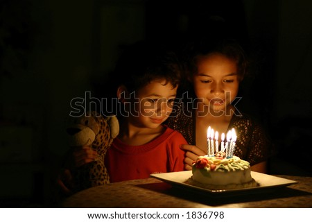 A brother and his sister sits in front of a birthday cake, all lit up with candles in the dark - stock photo