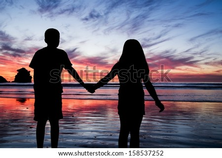 A brother and sister holding hands at sunset in Morro Bay, CA - stock photo