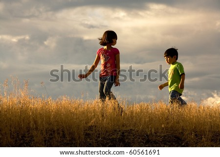 A brother and sister in their own little adventure walk. - stock photo