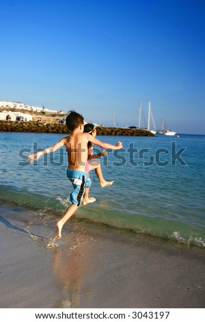 A brother and sister racing towards the sea on a warm evening by a tropical beach.