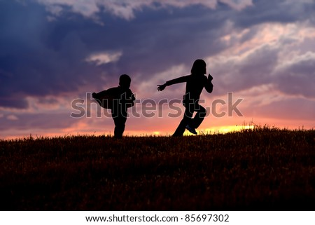 A brother and sister run and play at sunset. - stock photo