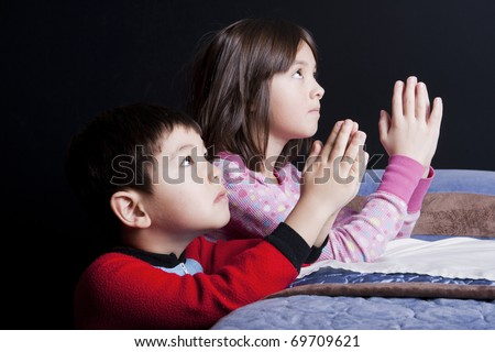 A brother and sister say their prayers just before bedtime. - stock photo