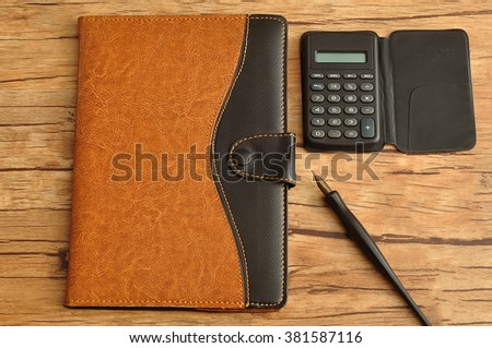 A brown and black leather note book displayed with a calculator and a fountain pen on a wooden background - stock photo