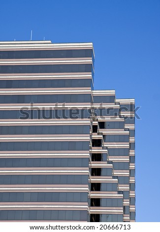 A brown and white glass office building against blue sky