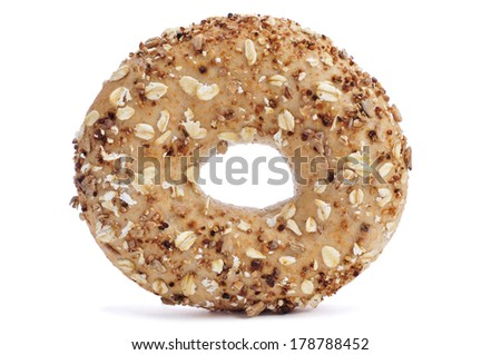a brown bagel topped with different seeds, such as sesame and poppy seeds, on a white background - stock photo
