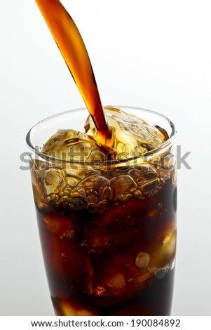A brown beverage being poured into a glass. - stock photo