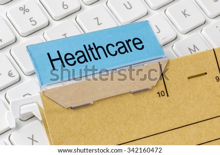 A brown file folder labeled with Healthcare - stock photo