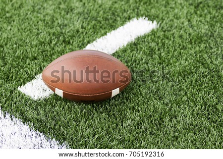 A brown football placed on a white hash mark on a green turf field.