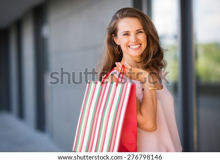 A brown-haired woman is seen from the waist up. She holds a striped, multi-coloured and red shopping bag over her right shoulder. Her smile is relaxed and happy.