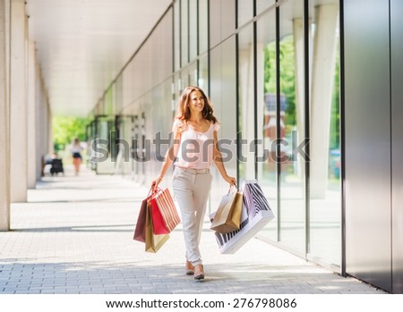 A brown-haired woman wearing muted, gentle colours holds five colourful, patterned shopping bags walks towards the doors of an exclusive shopping mall.