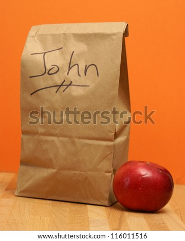 A brown lunch bags prepared specially for John. - stock photo