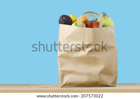 A brown paper shopping bag, filled to the top with varieties of fruit, on a light wood surface.  Isolated on a turquoise blue background. - stock photo