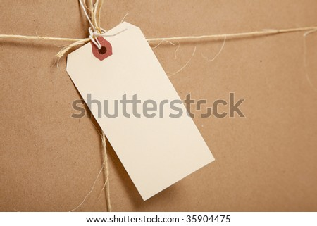 A brown shipping box tied with twine or string with a blank shipping label with copy space - stock photo