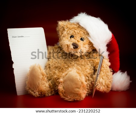 A brown teddy bear wearing a Christmas hat sitting and writing a letter with wishes to Santa Claus isolated against a black and brown background. - stock photo