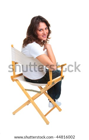 A brunette woman in casual clothing sat on a directors chair looking back over her shoulder, isolated on a white background.