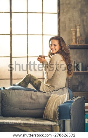 A brunette woman in comfortable clothing is is smiling and holding a hot cup of coffee, sitting on the back of a sofa. Industrial chic background, and cozy atmosphere. Loft decoration details.