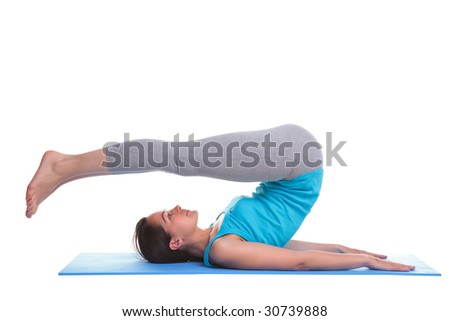 A brunette woman lying on a yoga mat doing a leg stretch exercise, isolated on a white background. - stock photo
