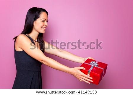A brunette woman wearing a black dress handing over a gift. - stock photo