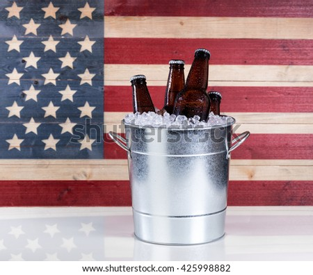 A bucket of cold bottled beer on ice with USA wooden flag in background.