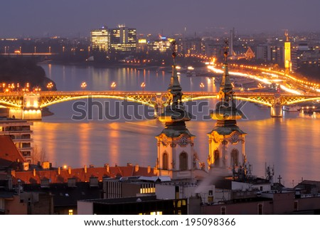 A Budapest view through Danube River just after sunset. St.Anna Church and Margaret Bridge are in the frame. Long exposure. - stock photo