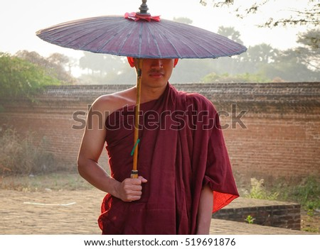 A Buddhist monk in the red robe with umbrella at the acient pagoda.