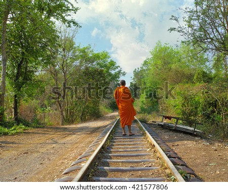 A Buddhist monk walks down a rail road track in Cambodia. The monk's face and identity is not visible and could be any monk. - stock photo
