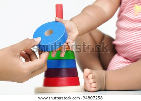 A building block being handed by an adult hand to a baby who is - stock photo