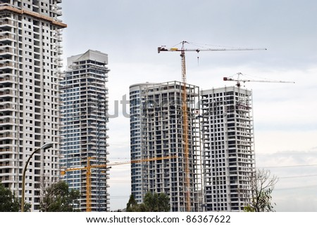 A Building cranes  and buildings  under construction - stock photo