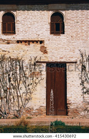 A building with stone walls and timber door / windows inside the Alhambra complex, Granada (Spain) - stock photo