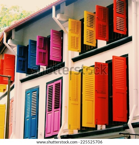 A building with window shutters painted in bright shades of blue, pink, yellow and red. - stock photo