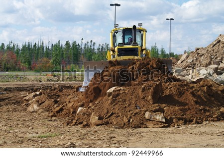 A bulldozer moving earth to level a pile of earth - stock photo