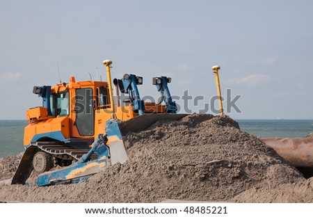 a Bulldozer the beach on a dredging project in holland - stock photo