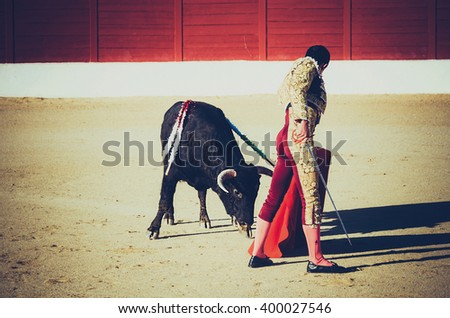 A bullfighter giving a pass to the bull with his cape. The matador confronts the bull with the capote. Vignette effect - stock photo